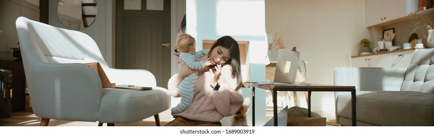 Young mother working from home surrounded by daughter and dog, having a work call. Stay home, quarantine remote work. Shot on RED Dragon