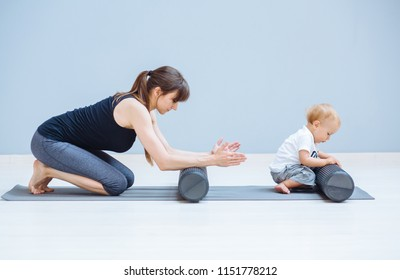 Young mother workout with foam rollers does physical pilates exercises together with her toddler baby boy. Fitness, happy maternity sport with children concept.