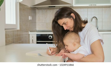 Young mother writes in a notebook and plans with baby in the kitchen at home
