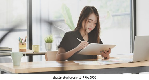 Young motivated female freelancer writing her idea in modern office