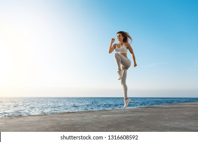 Young motivated happy sporty female runner fitness instructor, jumping, excercise near sea enjoying fresh morning air training, smiling facing sunlight, workout wearing activewear, running in quay
