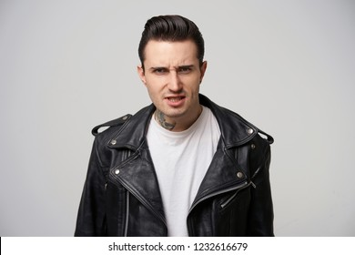 A young motorcycle racer looks angry, argues, defends his opinion, eyebrows frowned, fiery eyes, mouth ajar, dressed in black leather jacket, with a stylish hairstyle in grease, over white background