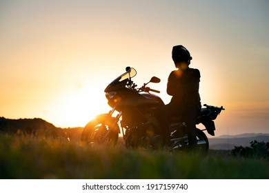 Young motorcycle rider on the road with sunset light background.