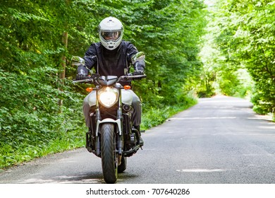 Young motorcyclist riding on a country road across a forest on a summer day