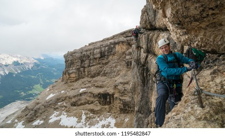 young mountain climbers on a steep Via Ferrata with a view of the Italian Dolomites