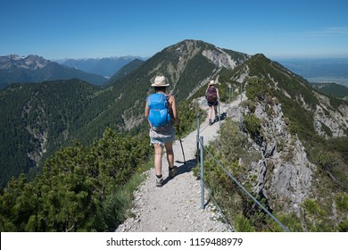 young mountaineering woman from the back, on adventurous mountain ridge herzogstand. hiking trail with safety rope