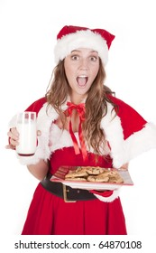 A young mrs Santa is holding a glass of milk and a plate of cookies.