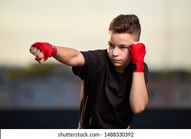 Young muay thai fighter or kickboxer training on the roof above the city