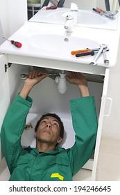Young mulatto plumber repairing sink in kitchen.
