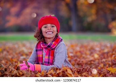 Young multi ethnic girl sitting in autumn leaves at a park