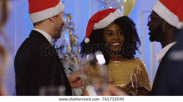 Young Multi ethnical friends in Santa Claus hats talking and drinking Champagne at the Christmas party. Christmas celebration. Indoors