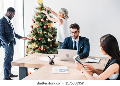 young multicultural businesspeople working and decorating christmas tree in office
