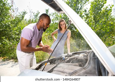 Young multiethnic couple broke down the car while traveling on the way to rest. They are trying to fix the broken by their own or should hitchhike, getting nervous. Relationship, troubles on the road