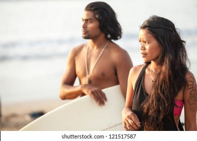 Young multi-ethnic couple on beach with surfboard in the tropics