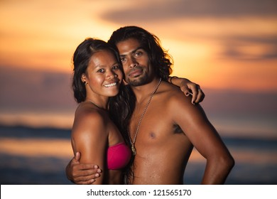 Young multi-ethnic couple on romantic beach at sunset in the tropics