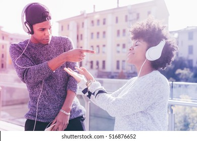 Young multiethnic couple outdoor in the city listening music with head phones - enjoying, music, relaxing concept