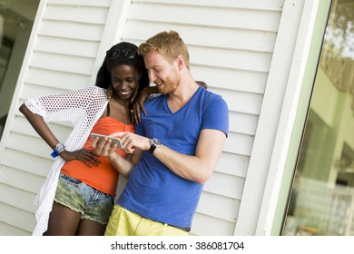 Young multiethnic couple with smartphone at summer