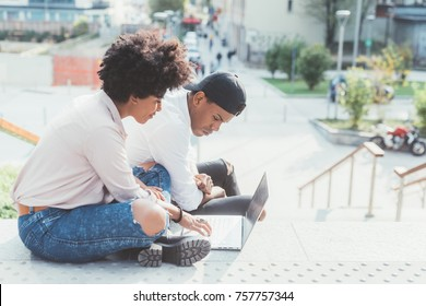 Young multiethnic couple using computer sitting outdoor in the city - business, technology, internet concept