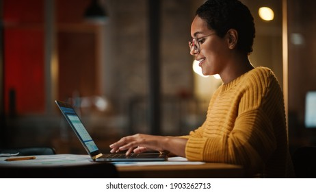 Young Multiethnic Developer Working on a Laptop Computer in Creative Office Environment. Beautiful Diverse Latin Female Project Manager is Developing Data and Scheduling a Project.
