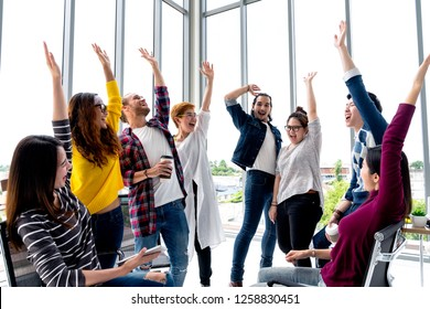 Young multiethnic diverse creative asian group huddle and high five hands together in office workshop with success or empower expression in teamwork. Young asian marketing team with copy space.