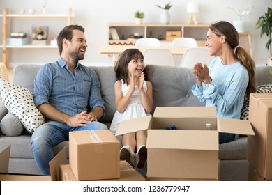 Young multi-ethnic family celebrate move at new modern wealthy home sitting together on couch in living room laughing smiling having fun clapping hands. First dwelling relocation and mortgage concept