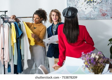 young multiethnic fashion designers looking at each other while working together