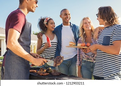 Young multiethnic friends having fun grilling meat enjoying bbq party. Group of happy guys and girls cooking and eating at barbecue dinner outdoor. Men and women standing around grill and chatting.