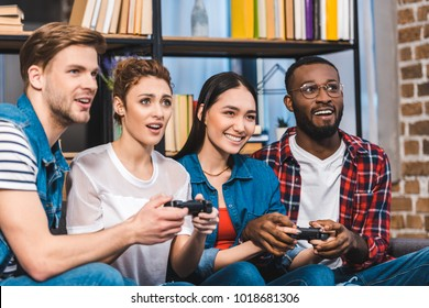 young multiethnic friends playing with joysticks together at home