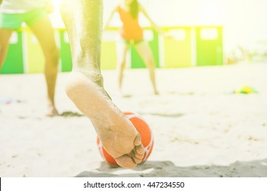 Young multiethnic friends playing soccer on the beach - Group of people playing football match on sand in summertime - Tourists having fun on vacation with sport beach games with back lighting