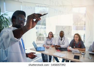 Junge, multiethnische Praktikanten hören Vorlesungen von afro-amerikanischen Ärzten auf der medizinischen Konferenz in der Klinik. Ärzte schreiben an Bord einige Formeln für Praktikanten im Konferenzraum im Krankenhaus bei Sonnenaufgang.