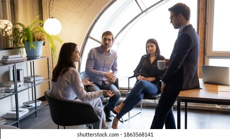 Young multiracial colleagues friends chatting talking discussing work company policy on informal meeting, diverse millennial managers mates have conversation sharing news ideas at break time in office