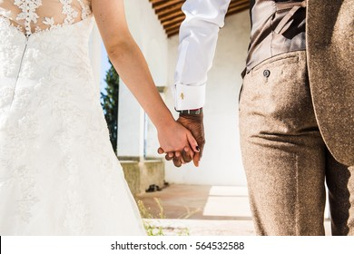 Young multiracial couple hand by hand in the day of their marriage