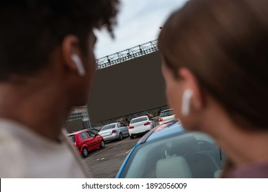 Young multiracial couple watching movie on autocinema screen while standing together on car parking, selective focus. Free time, leisure and entertainment concept