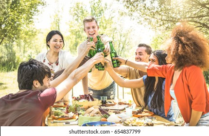 Young multiracial friends toasting at barbecue garden party - Friendship concept with happy people having fun at backyard bbq summer camp - Food and drinks fancy picnic lunch - Focus on beer bottles