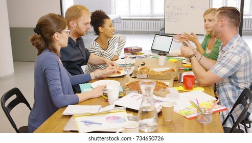 Young multiracial group of people posing at wooden table in office and eating ordered pizza while enjoying conversation.
