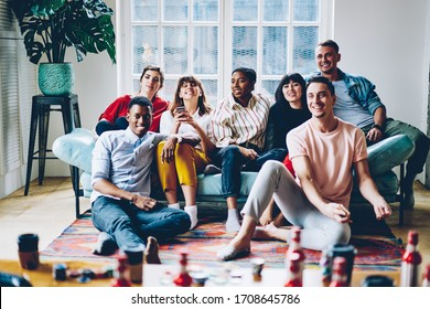Young multiracial people in trendy colorful clothes watching television and laughing while relaxing together in cozy modern apartment during meeting in day off