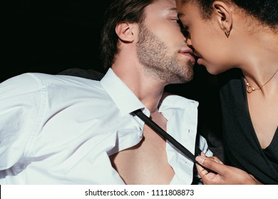 young multiracial sexy couple in black clothing kissing on dark background
