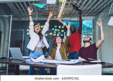 Young multiracial women and men tossing papers and documents up while celebrating successful project idea coworking in team in modern office