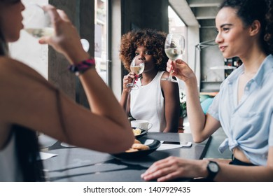 young multiracial women sitting in modern restaurant drinking together wine – friendship, cheerful, communication