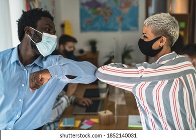 Young multiracial workers wearing face mask doing new social distance greetings bumping elbows inside co-working creative space - Focus on male hand