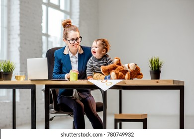 Young multitasking businessmam dressed in the suit working with laptop and documents sitting with her baby son at the office