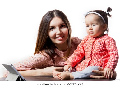 Young mum embraces a daughter on a light background in bright clothes