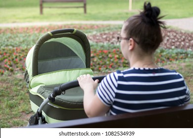 Young mum sitting, holding pram in park.