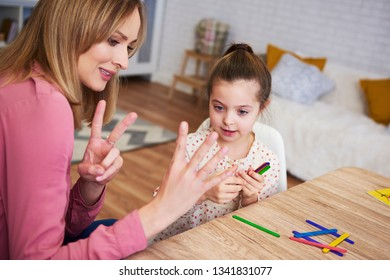 Young mum teaching child to count at home