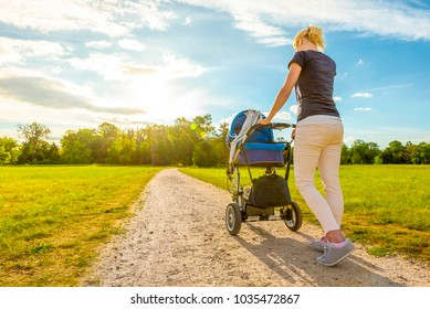 Young mummy carries a baby buggy in the beautiful royal gardens