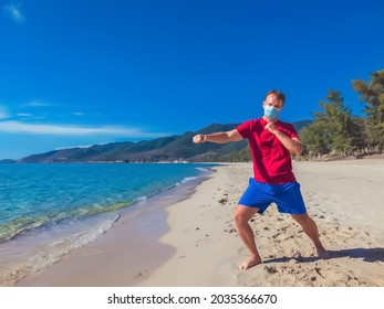 Young muscle man in medical mask perform outdoor workouts in the park near sea during wave coronavirus Covid 19 pandemic quarantine. Kick training pose, swing arms and legs, sport active life