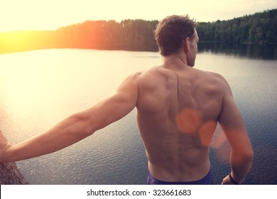 Young and muscle man standing on the cliff near the water outdoors and looking far away (intentional sun glare and lens flares)