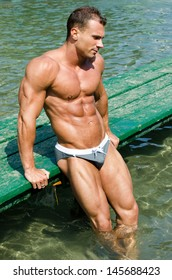 Young muscle man standing with sea or ocean behind showing muscular torso, pecs, arms and abs