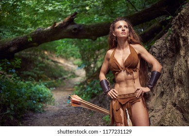 young muscular amazon girl walks through a deciduous forest.