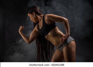 Young muscular asian woman posing on black background